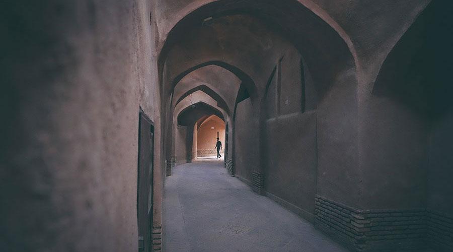 Photograph of a man walking through a tunnel.