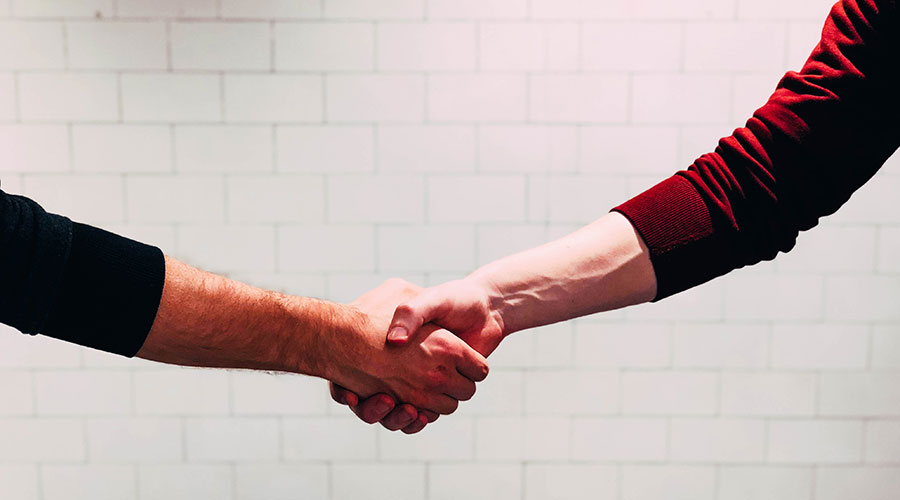 Photograph of a handshake with a white wall on the background.