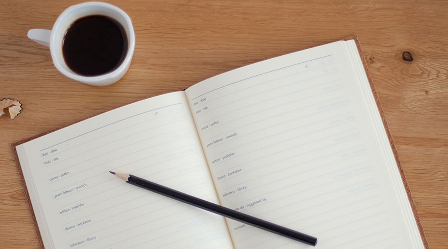 Top down photograph of a notebook, pencil and a cup of coffee.