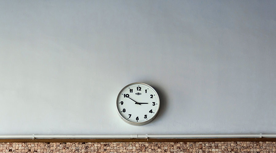 Photograph of a clock on a white wall.